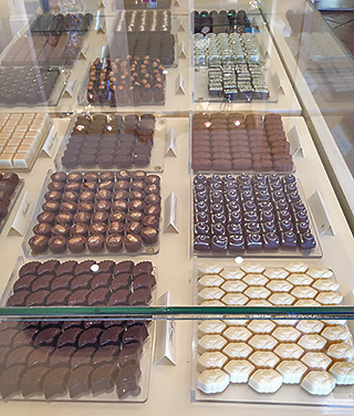 Fancy chocolates fill glass cases in the upscale chocolatier's boutique.
